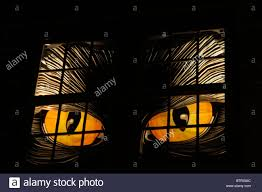 huge scary eyes light up the window of a halloween decorated