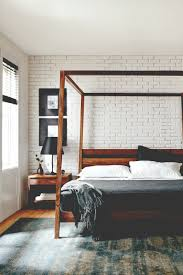 white washed brick complements a minimal wooden bed frame in this