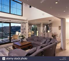grey l shaped sofa in modern double height spanish living room