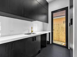 white kitchen cupboards black bench custom laundry black cupboards white bench cupboard