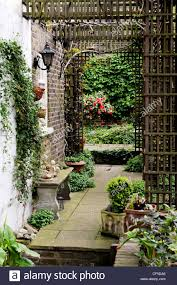 hidden treasure paved walkway with arched trellis potted plants