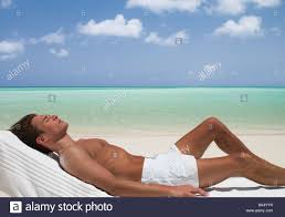 Beach Lounge Chair Man On Beach Sunbathing On Lounge Chair With Eyes Closed Stock