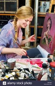 a painter blonde woman with paint brush and canvas in a painter studio stock