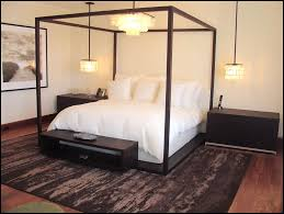 black bedstead with canopy and chandelier also pendant lamps dark