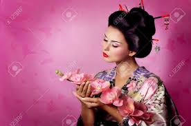 Geisha in flamboyant kimono protecting her makeup with a fan  Kyoto  Japan