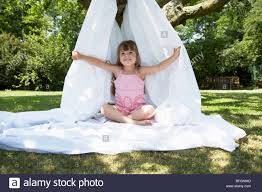 young in backyard sitting in tent made of bed sheet stock