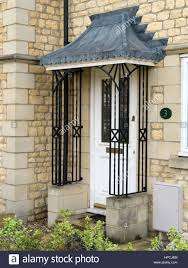 house front door with ornate wrought iron porch railings and lead