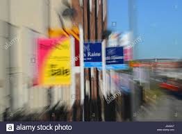 conceptual image showing house for sale signs by new houses