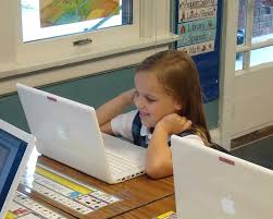 little girl sitting in front of a computer