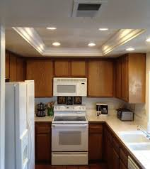 small kitchen illuminated with recessed tray ceiling lighting