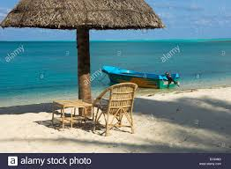 Beach Umbrella And Chair Thatched Beach Umbrella Empty Rattan Chair And Table With Boat On