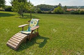 Wooden Recliner Chair Comfortable Wooden Recliner Chair On A Lush Green Lawn In A Rural