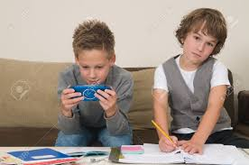 two friends doing their homework in the livingroom one of them