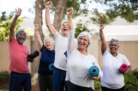 le stuoie anziani multi etnici allegri con le stuoie di esercizio al parco