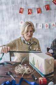 what to get an elderly woman for christmas elderly woman decorating the christmas present stock photo