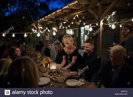 waitress serving food to friends at outdoor dinner harvest party