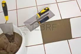 worker with notched trowel install tiles with tile adhesive