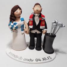 a man united and manchester city themed golf wedding cake topper