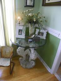 concrete seahorse birdbath base turned into a corner table in our