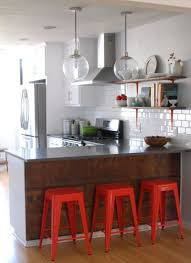 house renovation update and kitchen ideas wood backed breakfast bar white subway tiles bright red stools via apartment therapy