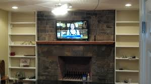 tv on the black wall panel combined with light brown wooden two