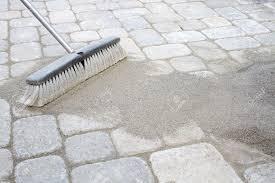 Patio Pavers Images by Broom Sweeping Locking Sand Into Backyard Patio Pavers Stock Photo