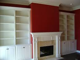classic white tone bookshelves and fireplace mantle mixed red wall