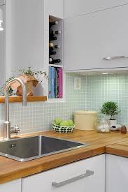 the mint colored tiles wooden built in shelf above sink that