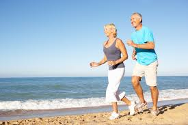 senior couple in fitness clothing running along beach ways and means