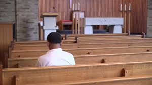 pan down to an empty church with one man praying stock video