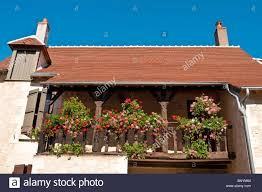 hanging baskets and planters on wooden balcony of renovated stone