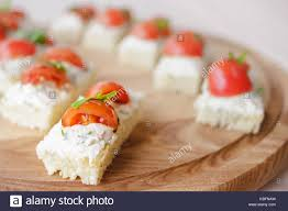 canapé cottage canape with cottage cheese basil and vine tomatoes on wooden plate