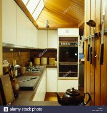 eye level oven and beech paneled ceiling in a sixties kitchen