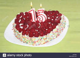 burning birthday candles number 15 on raspberry cake stock photo