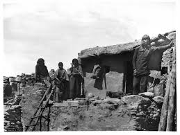 file four members of a hopi indian family on top of an adobe house