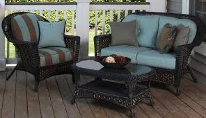 black wicker outdoor furniture throughout patio with blue cushions