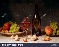 classic still life featuring a colorful bowl of fruit and a wine