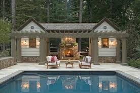 outdoor kitchen with stone fireplace transitional pool