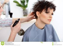 hairdresser doing hairstyle brunette with short hair in salon