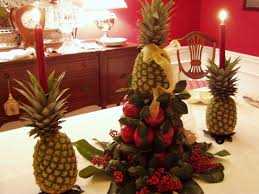 red apples and pineapples arrangng combined with red candles above