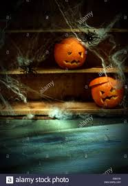 two halloween jack o lanterns carved from oranges and spiderwebs