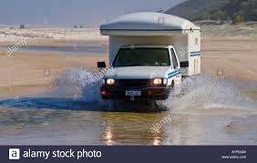 offroad camper off road camper 4x4 rv driving through the water on the beach at