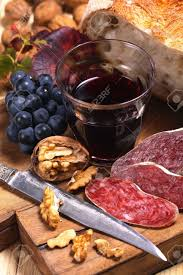country sack arrangement of salami bread wine nuts and grapes