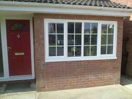 exterior garage conversion with paint front door and brick wall