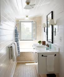 narrow bathroom with glossy white tongue and groove walls and