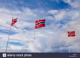 norway norwegian flags waving on blue sky background stock photo
