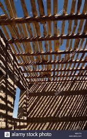 striped shadows of wood ceiling beams and slats on mud brick walls