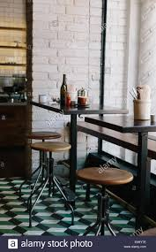 wood table and bar stools at modern restaurant with exposed white