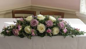 ceremony table flower arrangement of ivory avalanch roses dusky