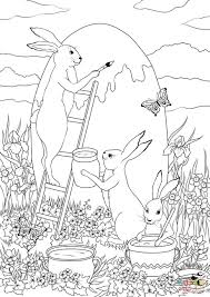 three easter bunnies are painting a huge easter egg coloring page
